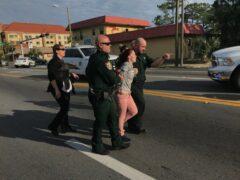 Deputies escorting woman in handcuffs.