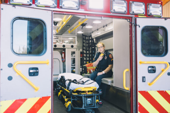 A paramedic uses a radio in the back of an ambulance