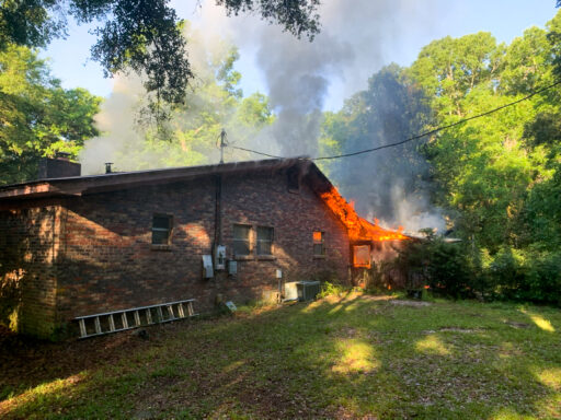 Flames coming from the back of a brick single-story home