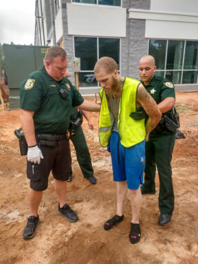 deputies patting down a light skinned black male with tattoos