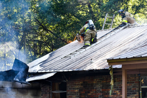 Firefighter using saw to cut into metal roof of brick home