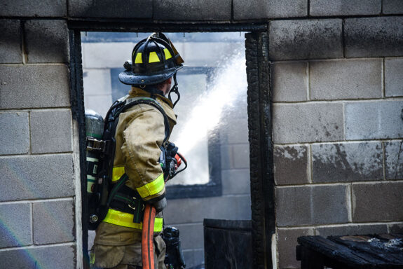 firefighter spraying water into garage of home