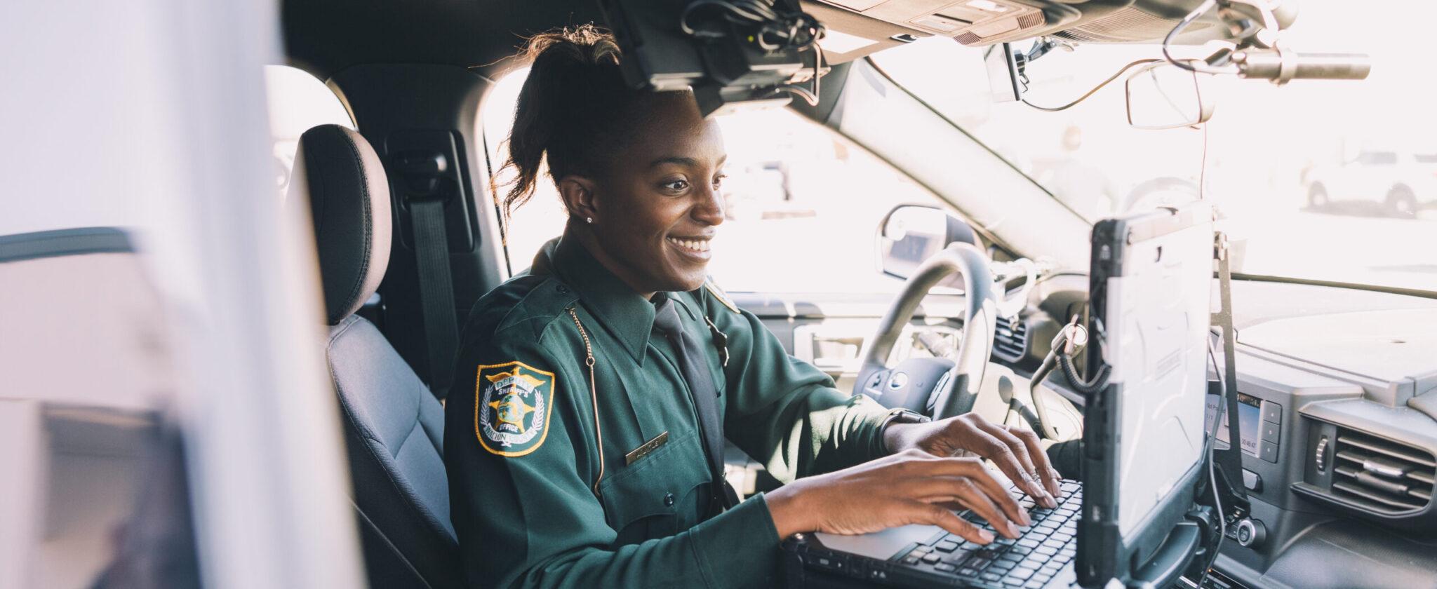 Black female officer typing on laptop inside law enforcement vehicle