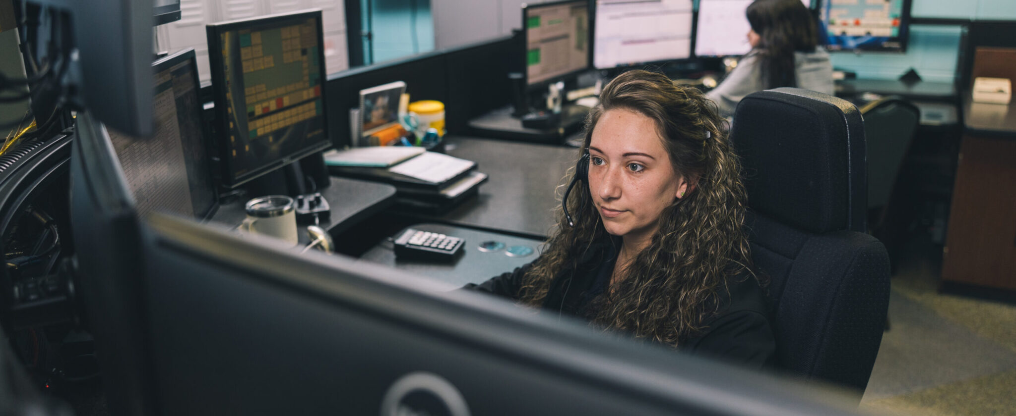 White female dispatcher sitting in front of computer with headset on