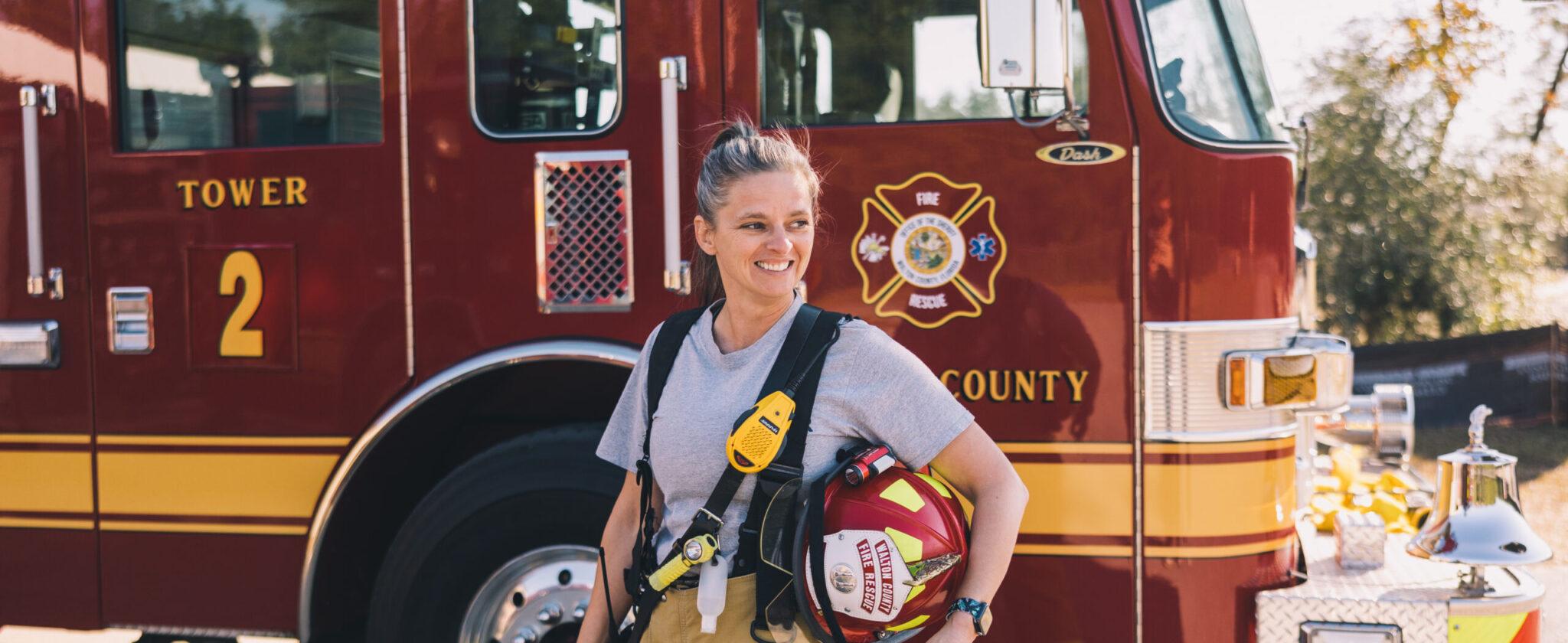 White female firefighter standing in front of fire engine holding helmet