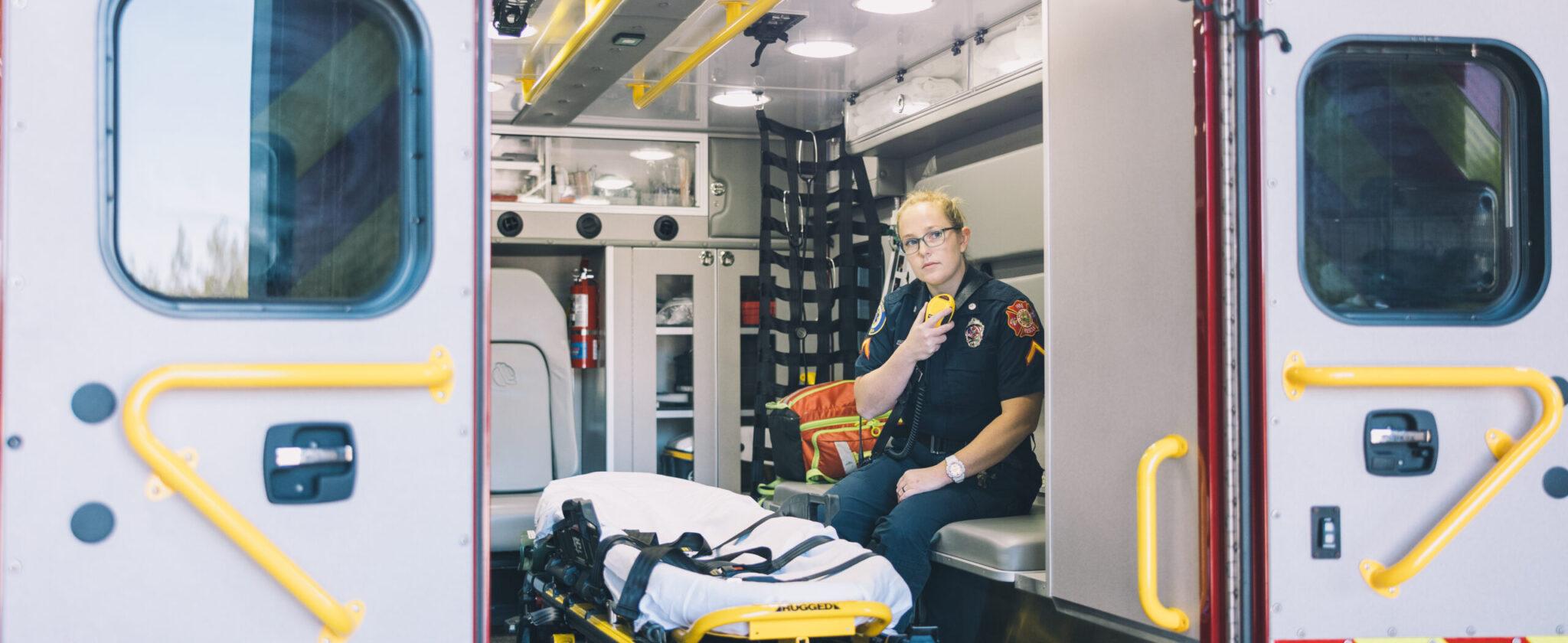 White female paramedic sitting in the back of the ambulance holding radio