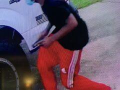 Black male wearing red pants carrying a handgun