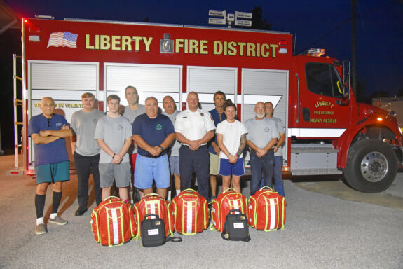 Volunteer Firefighters and Walton County Fire Rescue Chief standing in front of Liberty fire truck with medical supplies