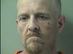Mugshot of white bald man with light colored goatee