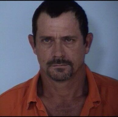white male with brown hair and brown goatee in an orange jumpsuit