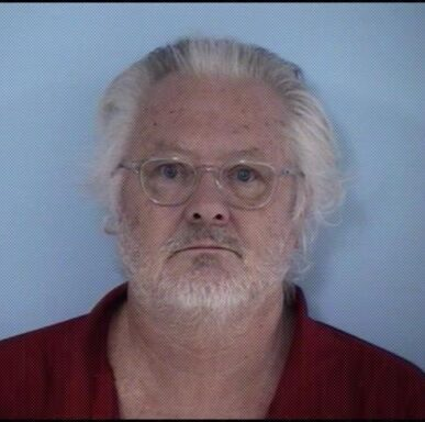 Mugshot of white male wearing clear rimmed glasses with white hair