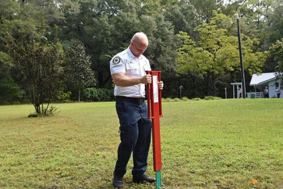 White male wearing fire officer uniform installing address sign in yard