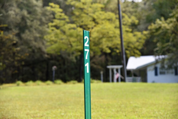 Green reflective sign with house numbers on it in yard in front of white home